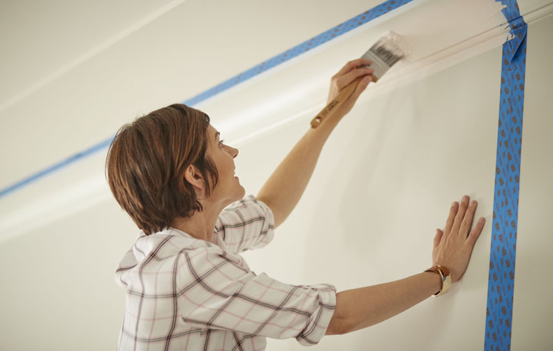 Woman painting wall with masking tape
