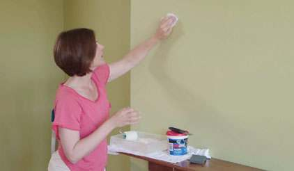 Woman prepping wall for paint