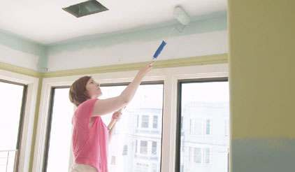 Woman using roller to paint ceiling