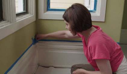 Woman putting masking tape on wall