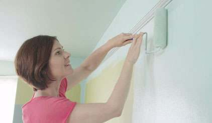 Woman rolling paint on wall